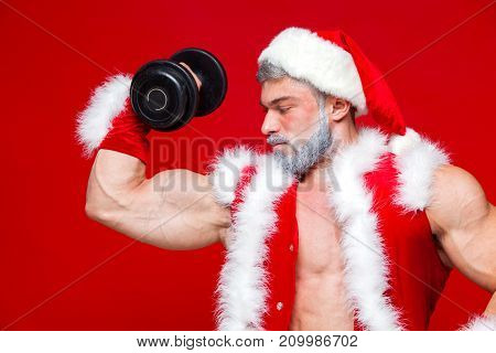 Holidays and celebrations, New year, Christmas, sports, bodybuilding, healthy lifestyle - Muscular handsome sexy Santa Claus.Isolated on red background