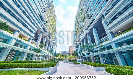 Low angle perspective view of empty pavement and modern office building with green eco concept balcony .