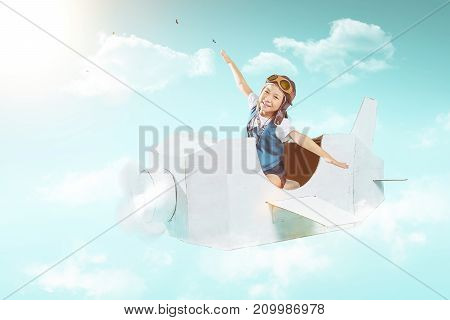 Little cute girl fly with a white retro style cardboard airplane on sky . Childhood dream imagination concept .