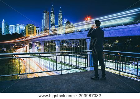 Businessman using phone on open terrace modern city with traffic light trails in downtown background .
