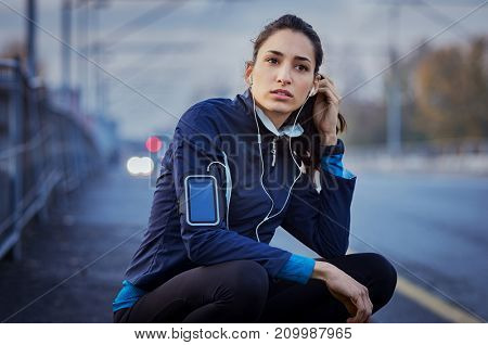 Young woman sitting on street resting at night. Woman athlete sitting on road while listening to music during jogging exercise. Beautiful girl relaxing after a long run in the city.
