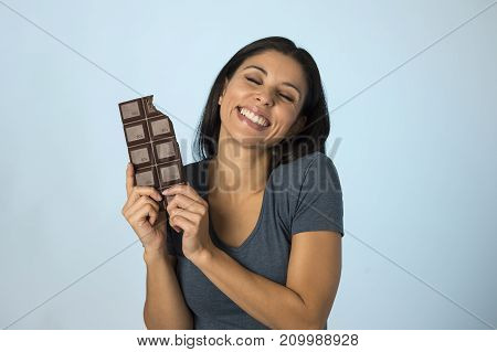 young attractive and happy hispanic woman in blue top smiling excited eating chocolate bar isolated background in diet calories and sugar addiction concept and sweet temptation concept