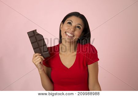 young attractive and happy hispanic woman in red top smiling excited eating chocolate bar isolated on pink background in diet calories and sugar addiction concept and sweet temptation concept
