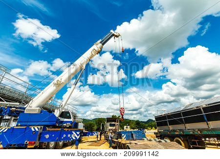 many Truck and Crane in yard site consist of lifting, pulley, sling, are ready for construction and blue sky
