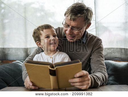Grandfather and grandson reading a book together