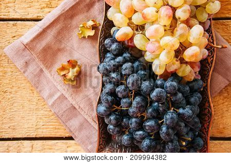Bunches of fresh ripe grapes served on a vintage tray on a wooden background. Close up and top view.