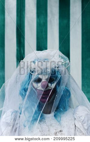 closeup of a scary evil clown wearing a dirty and ragged bride dress in front of the tent of a circus, with a negative space on top