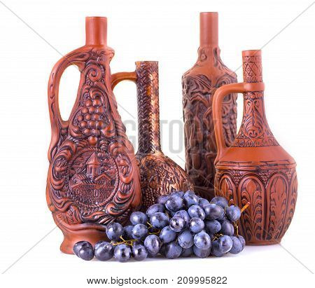 clay bottles and grapes on a white background