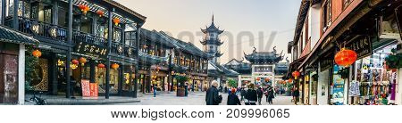 Suzhou, China - Nov 5, 2016: Panorama of shopping street at the historic Zhouzhuang Water Town. Numerous visitors can be seen walking along this path.