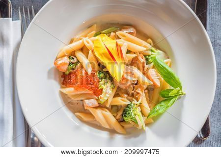 Tasty penne with juicy salmon and caviar in restaurant