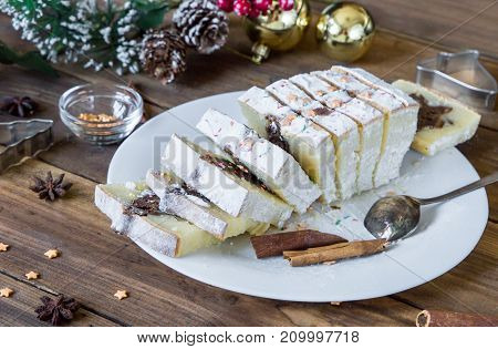 slicesed christmas cake on the background with holidays decorations with cinnamon and stars