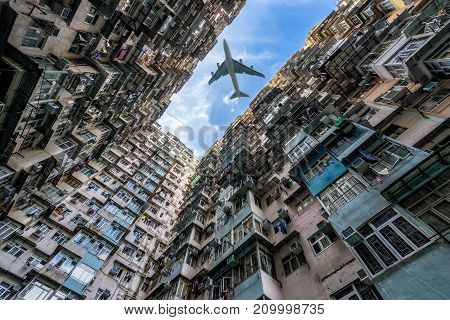 HongKong. Airplane flying over old tall and dense residential building in Hong Kong.