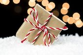 Small gift box wrapped in brown paper and twine wedged in white snow. Black background with soft holiday lights. Christmas holiday sale or event concept poster