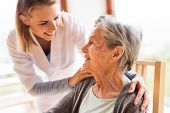 Health visitor and a senior woman during home visit. A nurse talking to an elderly woman. poster