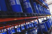 system of address storage of products, materials and goods in a warehouse. blue plastic barrels for storage of chemical liquids and products. Modern warehouse and storage systems. poster