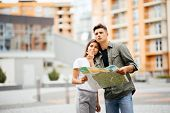 Portrait of an attractive tourist young couple relaxing sightseeing and visiting a destination city on holiday pointing up and enjoying traveling together outdoors poster