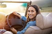 Happy woman holding steering wheel ready to drive and looking back. Smiling mature woman driving convertible car and looking at camera. Carefree woman enjoying driving in a cabriolet.  poster