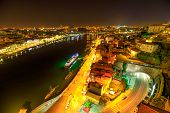 Aerial view of Oporto skyline and Ribeira Waterfront from Dom Luis I Bridge at night. Picturesque urban cityscape of Porto in Portugal.Rabelo and tourist boats on Douro River. Porto colorful nightlife poster