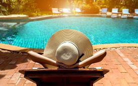 Bikini woman sexy in pool relaxing young asian beautiful female resting in vacation on summer season with hat at resort swimming pool edge with chair beach on side