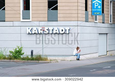 Bad Homburg, Germany - June 09: A Young Unknown Woman Is Sitting In Front Of The Karstadt Department