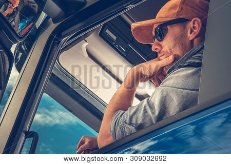 Caucasian Truck Driver In His 30s Inside Semi Cabin. Transportation And Logistics Theme.
