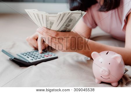 Close-Up of Beautiful Woman is Calculating Finance Money Saving and Investing on Her Bedroom. Woman Hands Holding Money Cash While Using Calculator, Business Financial and Investment Concept.