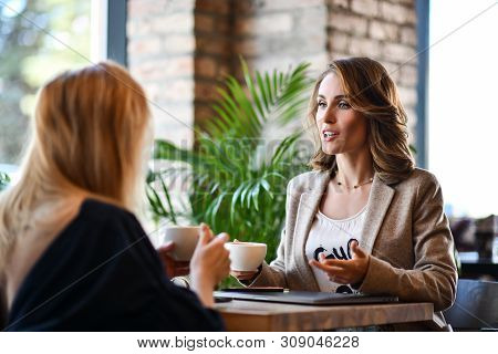 Two Young Business Woman Sitting At A Table In A Cafe. Girls Communicate And Discuss Matters. Friend