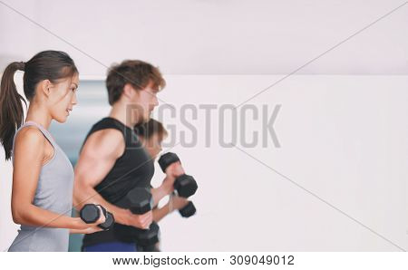 Gym training fitness people lifting weights in weightlifting group class in studio. Couple strength training at indoor workout. Woman lifting dumbbells training biceps in focus.