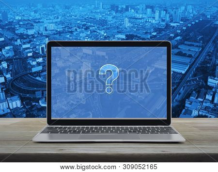Question Mark Sign Icon With Modern Laptop Computer On Wooden Table Over City Tower, Street, Express