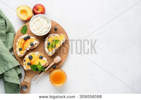 Ricotta And Fruit Bruschetta. Toasted Baguette Bread With Ricotta Cheese, Peach, Honey And Blueberry