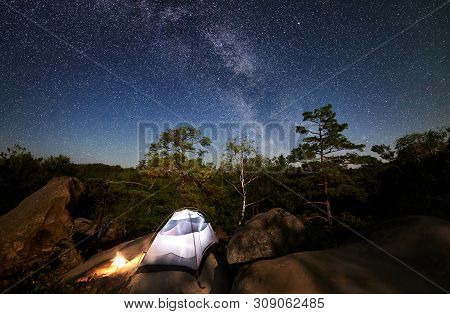Tourist Camping At Summer Night On Rocky Mountain. Glowing Tent And Campfire Under Wonderful Night S