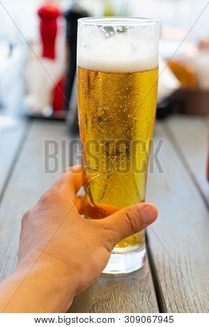 Close Up Picture Of Man Holding Cold Draught Beer At A Restaurant