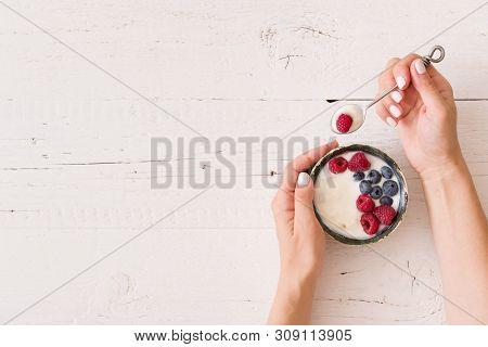 Top View On Girl Hands With A Bowl Of Yogurt. Young Woman Eating Organic Yogurt With Fresh Berries O