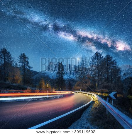 Milky Way Over Mountain Road. Blurred Car Headlights On Winding Road In Autumn. Colorful Night Lands
