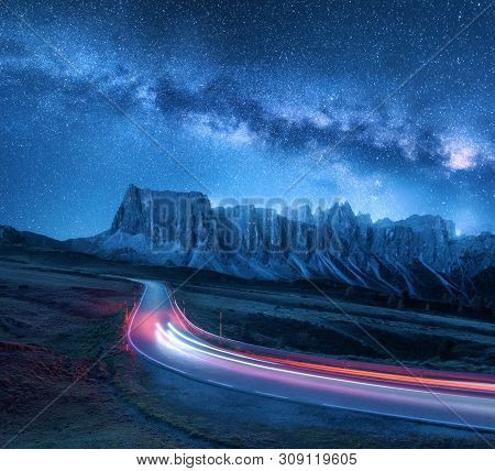 Milky Way Over Mountain Road At Night In Summer. Blurred Car Headlights On Winding Road. Colorful La