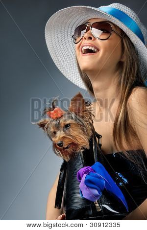 Profile of young glamor woman with Yorkshire Terrier dog in her bag poster