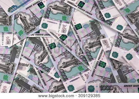 Russian Banknotes In Denominations Of A Thousand Rubles Are Scattered On A White Table In Disarray.