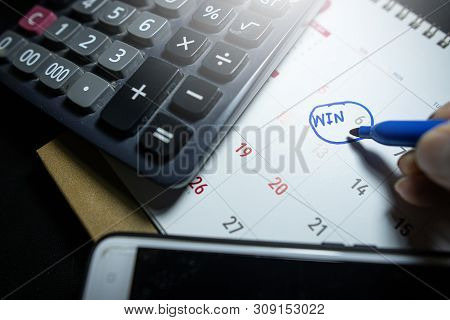 The Businessman Writes (win) On The Calendar