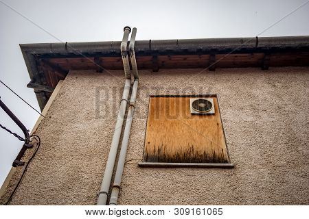 Chipboard wood covered window with old big windowed electrical fan on the back side of a city building, Ioannina downtown, Greece poster