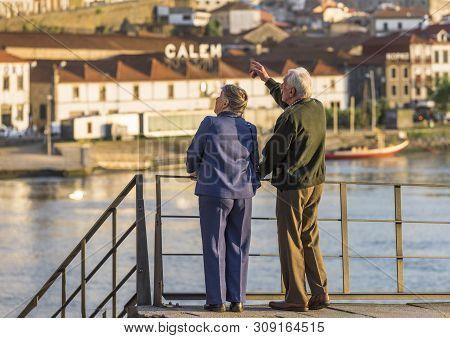 Porto, Portugal - April 2018: Senior Couple At The City Promenade