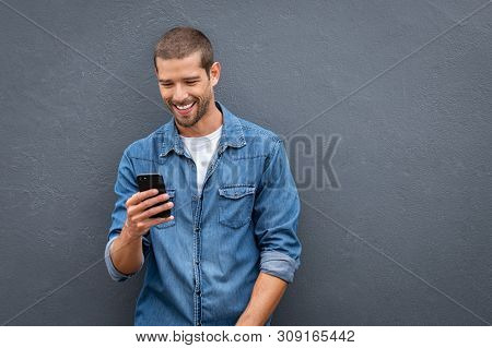 Young man leaning against a grey wall using mobile phone with copy space. Happy casual guy messaging on smartphone on gray background. Cheerful man typing and reading a message on cell phone.