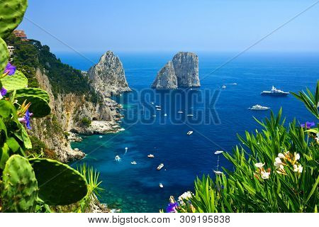 Capri Coast View With The Faraglioni Rocks, Flowers And Boats In The Blue Sea, Italy
