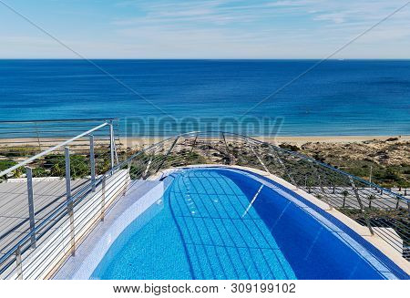 Waterside View Part Of Swimming Pool And View To The Sandy Beach Mediterranean Sea. Province Of Alic