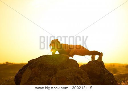 Young Woman Doing Push-ups on the Rock in the Mountains. Workout Exercise Against a Hot Beautiful Summer Sunset. Sport and Healthy Active Lifestyle Concept.