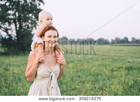 Mother And Baby Outdoors. Family On Nature. Loving Woman With Child In Countryside. Photo Of Natural
