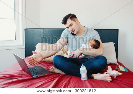 Angry Busy Caucasian Father With Newborn Asian Chinese Baby Working From Home. Male Man Parent Holdi