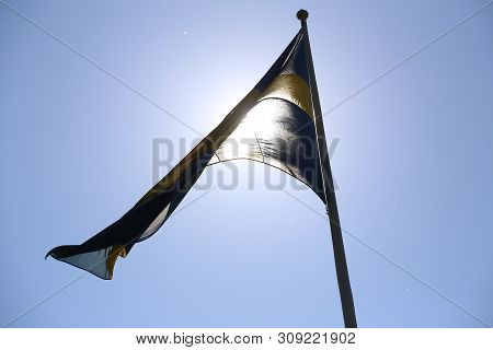 Swedish Flag Flying In The Wind Backlit By The Sun.