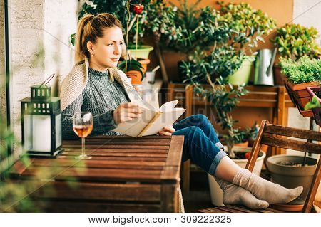 Young Beautiful Woman Relaxing On Cozy Balcony, Reading A Book, Wearing Warm Knitted Pullover, Glass
