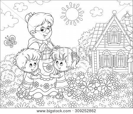 Granny And Her Little Grandchildren Smiling And Hugging Among Flowers On A Lawn In Front Of A Villag