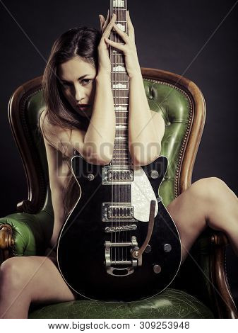 Photo Of A Beautiful Young Nude Woman Sitting On A Leather Chair And Posing With Electric Guitar.